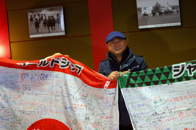 Naosuke Sugai, trainer of Gold Ship, holds flags signed by Japanese fans at a press conference in Chantilly on Oct. 1. Photo: AP Photo/Thibault Camus.