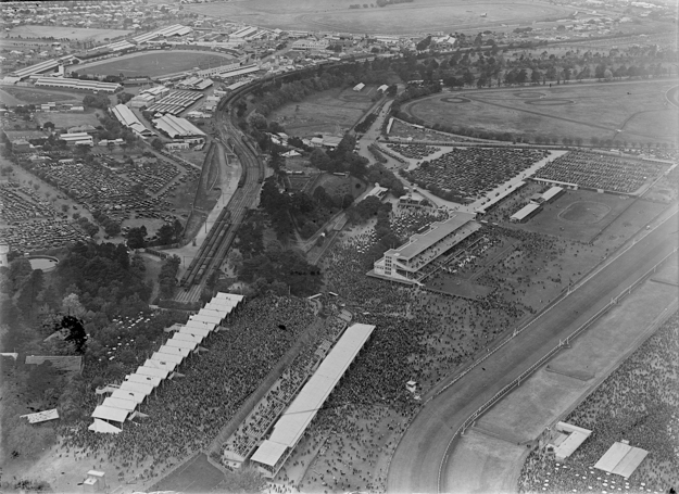 Flemington aerial view circa 1930, showing the Hill Stand and Bagot's Cowshed in the foreground and the 1924 Members' Stand beyond. Photo via State Library of Victoria.