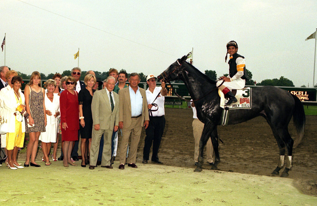 Holy Bull and connections in the winner's circle after the 1994 Haskell. Bill Croll, tan suit, no tie; Jimmy Croll, tan suit, tie; Billie Rae Croll, black and white sleeveless dress. Photo: Equi-Photo