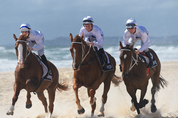 Jockeys (left-right) Brenton Avdulla, Tommy Berry and Tim Bell on Surfer's Paradise beach during the barrier draw festivities for the 2014 Magic Millions festival. Photo: Magic Millions.