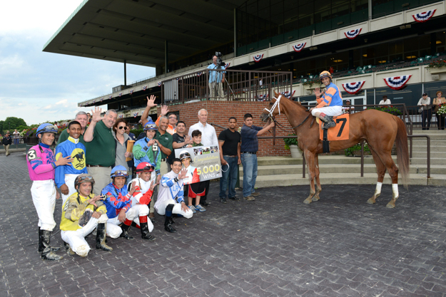 New York jockeys join John Velazquez on Galloping Giraffe in the winner's circle at Belmont Park after his 5,000th win. Photo: NYRA/Adam Coglianese.