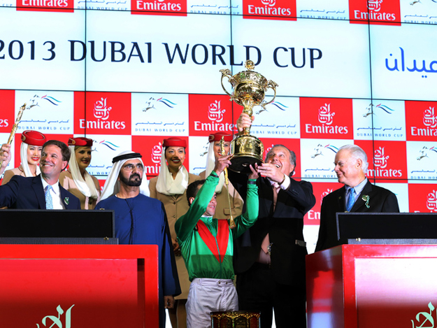 Jockey Joel Rosario and Arrowfield Stud's John Messara hoist the winner's trophy following the 2013 Dubai World Cup. Photo: RacingFotos.com.