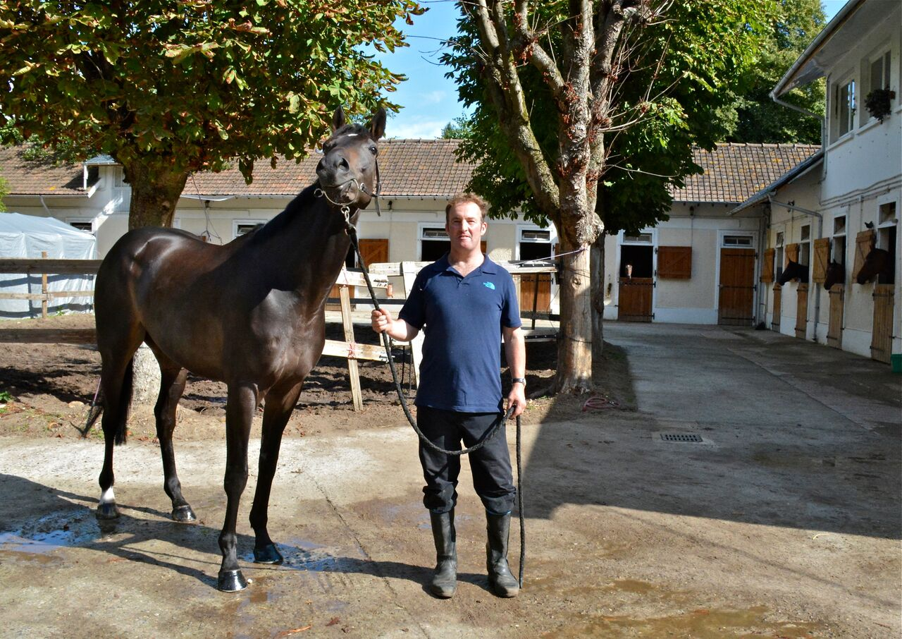 "Andrew Hpllinshead with Flying Cape at his rented stables in Lamorlaye. ""We love the lifestyle here in France,"" he says. Photo: Alex Cairns (www.winningpost.net); Twitter: @ACHorseRacing; Instagram @the_winning_post"