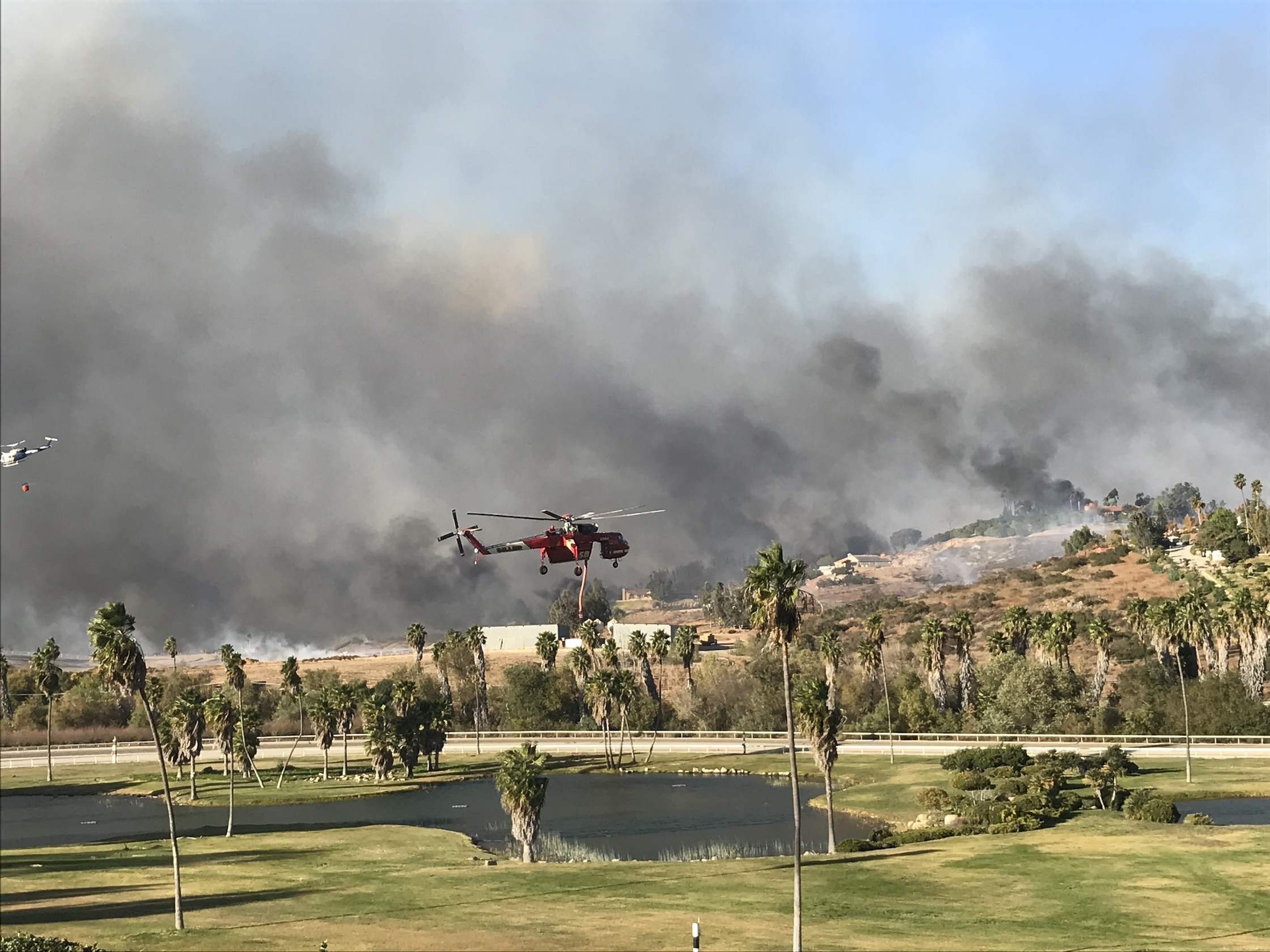 A helicopter arrives to suck water from the ponds at the Trifecta Equine Athletic Center, which is then taken to douse the raging wildfire