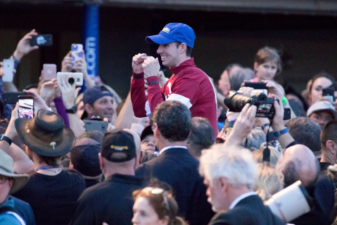 Photo shoot: Florent Geroux and Gun Runner (mainly hidden) are surrounded by racegoers as they return after their triumph. Photo: Mason Kelley