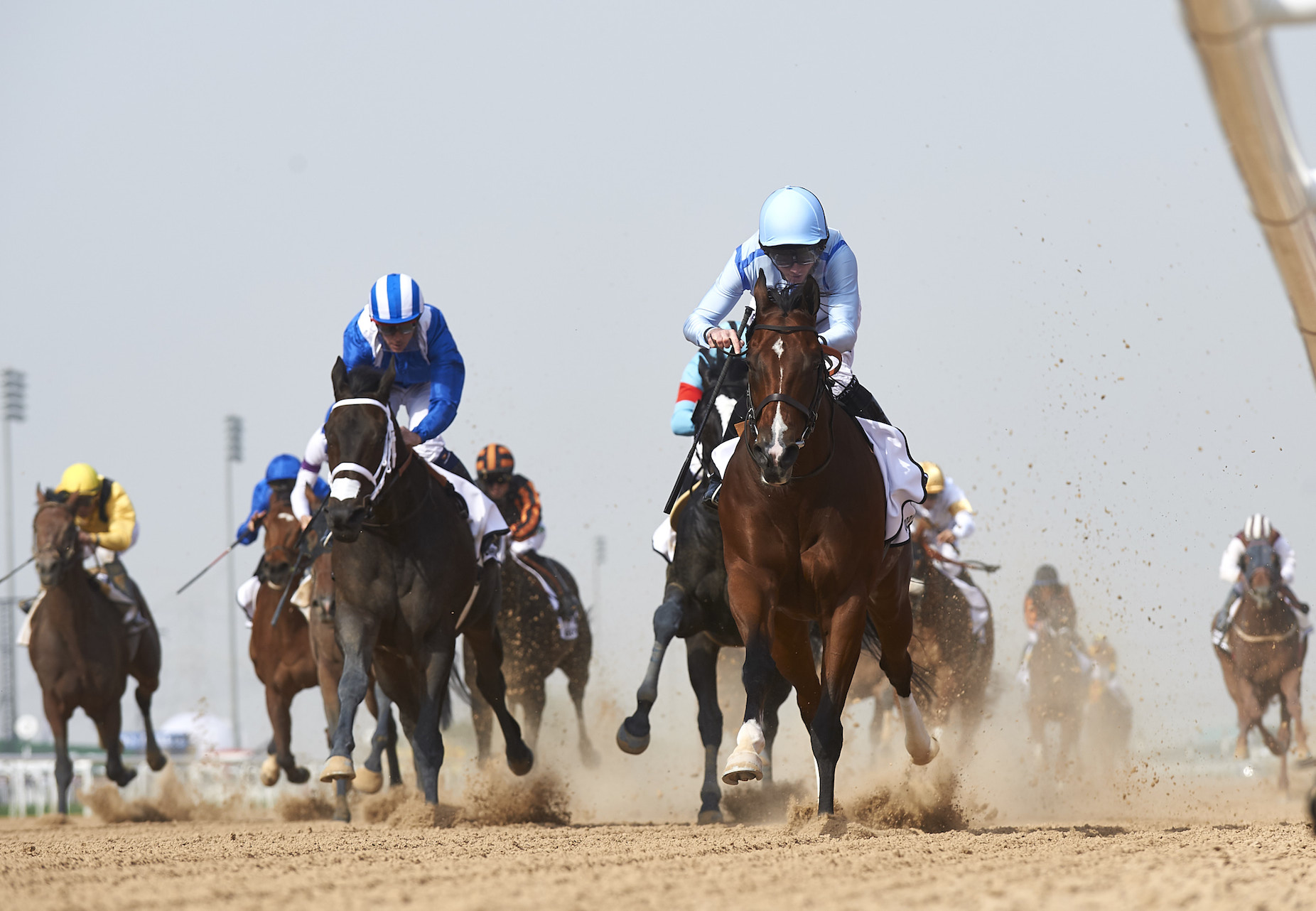 Ryan Moore (pale blue cap) took Heavy Metal into the lead soon after the gate opened in the Godolphin Mile, stuck to the inside and never looked like being beaten. Photo: Dubai Racing Club/Andrew Watkins